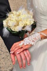 Mains avec alliances de jeunes mariés tenant un bouquet