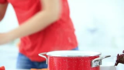 Woman in kitchen preparing soup