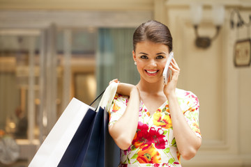Cheerful young woman calling by phone