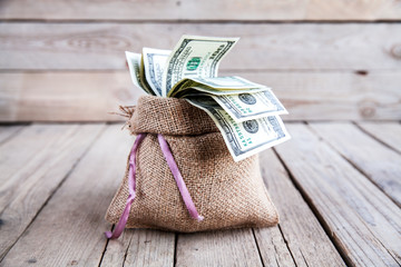 money in burlap sack on wooden background