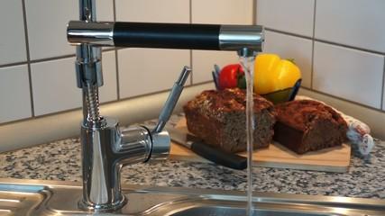 Wasserhahn mit fließendem Wasser und Brot