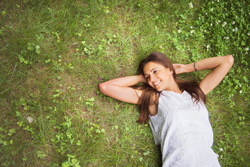 Young brunette woman enjoying the lying on her back on the green