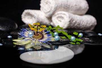 spa concept of passiflora flower, branches, towels, zen basalt s