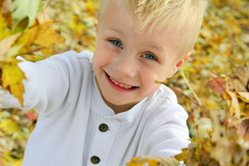 Happy Young Child Playing Outside with Fallen Autumn Leaves