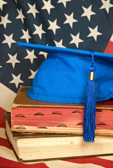 blue graduation cap on books with flag