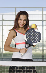 Paddle tennis woman player posing with racket and ball