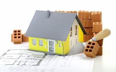 Gelbes Haus mit Plan und Ziegelsteinen