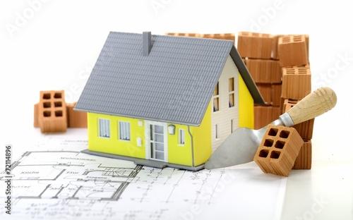 canvas print picture Gelbes Haus mit Plan und Ziegelsteinen
