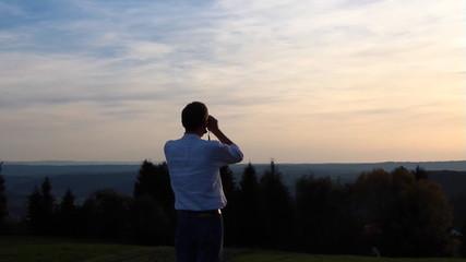 Mann mit Fernglas beobachtet Horizont