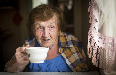 Old woman drinking tea at the window in his house..