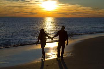 Couple walking on the oak island north carolina beach at sunset
