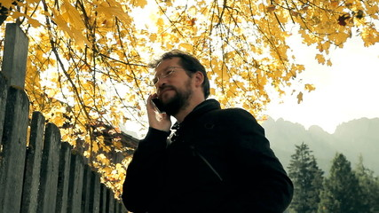 Man in front of mountain in autumn talking on phone
