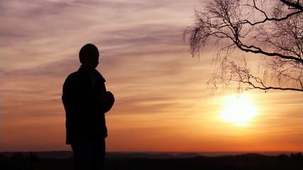 Mann beobachtet Landschaft bei Sonnenuntergang