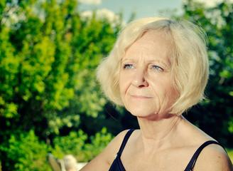 Mature, blonde woman in garden.
