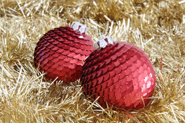 Two red Christmas baubles on golden tinsel