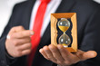 Man in a suit with tie holding an hourglass - 72119407