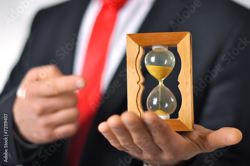 Leinwanddruck Bild Man in a suit with tie holding an hourglass