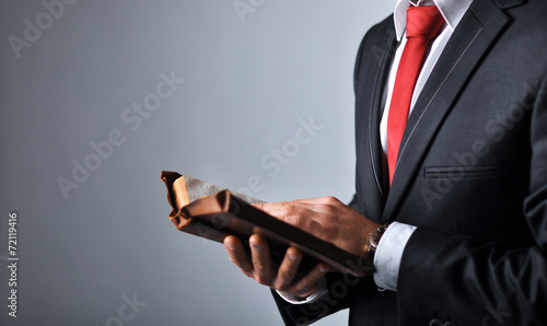 Businessman in a suit holding a book - 72119416