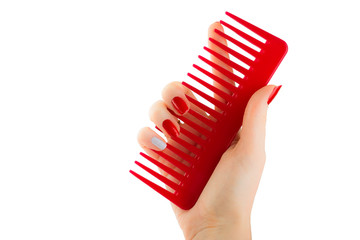 Female hand holding a red comb on a white background