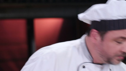 Middle-aged chef cooking in kitchen, white uniform, restaurant