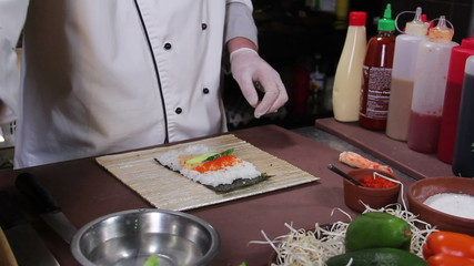 Chef making delicious sushi rolls with cucumber and red caviar