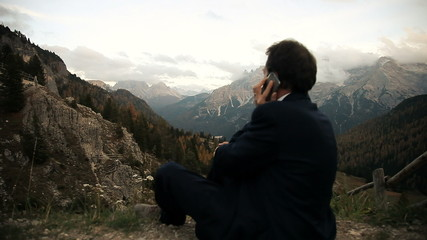 Happy business man on the phone in the mountain