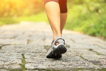 young fitness woman hiker legs walking on forest trail