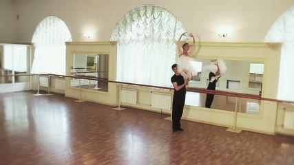 Ballet dancers in the studio, man carrying woman on shoulder