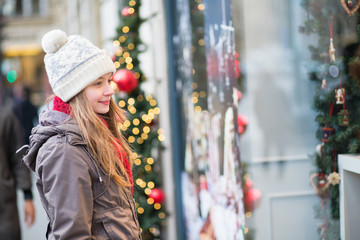 Girl looking at shop-windows decorated for Christmas
