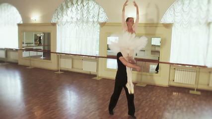 Elegant couple practicing ballet moves in studio, slow-motion