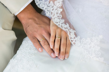 Hands with rings against wedding dress