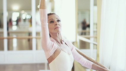 Elderly ballerina holds on to barre and practices ballet moves