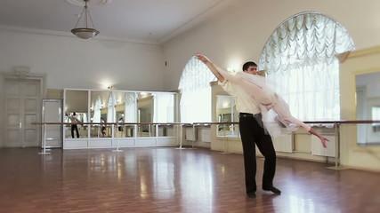 Ballet dancing, young male dancer twirling ballerina around
