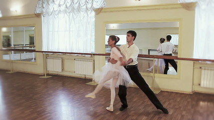 Young man dancing classical ballet with elderly woman in gym