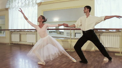 Elderly ballerina practicing ballet with young male, slow-mo