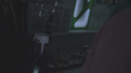 Young male bartender serving drinks at the bar in nightclub