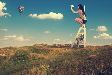 Girl climbing on a wooden staircase launches paper airplanes