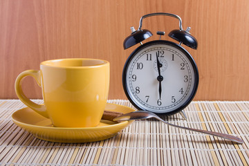 Still life with yellow cup and alarm clock on the table.
