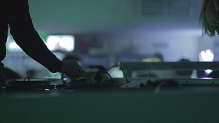 Male dj tweaking controls on sound board, nightclub atmosphere