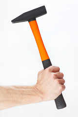 Hand of a joiner holding a hammer on a white background