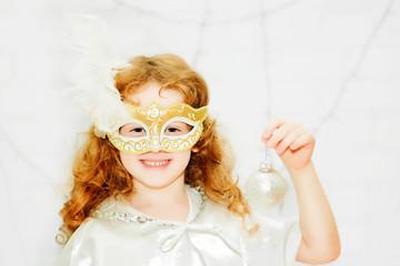 Portrait of a curly little girl in venetian mask on a light back