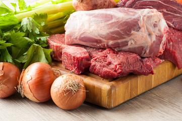 Tagli di carne bovina e suina cruda appoggiati sul tagliere