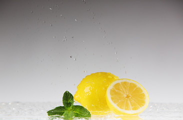 whole and sliced ​​lemon in a spray of water