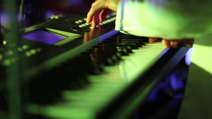 Musician playing on keyboards close up