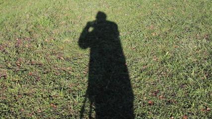 Schatten eines Fotografen auf Grasoberfläche