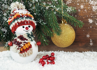 Snowman with Christmas tree on a wooden background