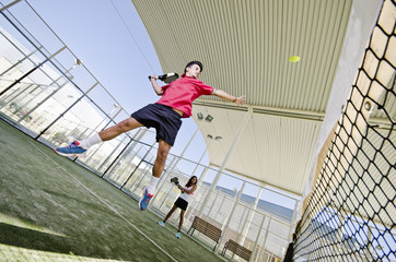 Paddle tennis player smashing the ball