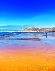 Orange und blauer Strand bei Ebbe