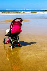 Einsamer Kinderwagen am Strand bei Ebbe