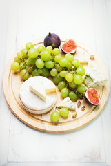 various types of cheese with grapes and figs